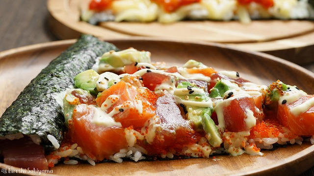 アボカド・サーモン・マグロの寿司ピザ、奥にチーズとトマトソースの寿司ピザが見える