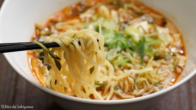 酸辣湯麺(サンラータンメン/スーラータンメン)の麺を箸でつかんだ様子