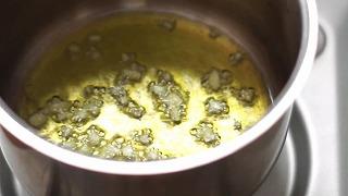 弱火でにんにくの香りをオリーブオイルに移す様子