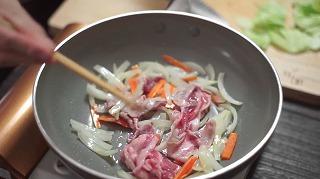 炒めた人参・玉ねぎに豚肉を加える様子