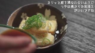 揚げ出し豆腐を盛り付けてつゆを注ぐ様子