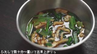茹で上がった小松菜・油揚げをつゆにひたす様子