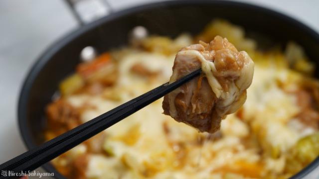 フライパンで作るチーズタッカルビの鶏肉を箸で持ち上げた様子