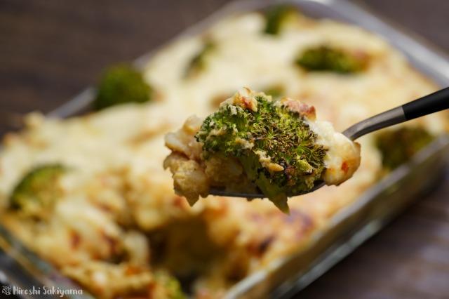キャベツとマッシュルームのクリームソースで作る、じゃがいもとブロッコリーのグラタンをフォークですくった様子