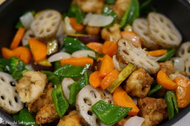 揚げた野菜・鶏肉と黒酢あんを絡める様子