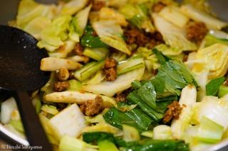 野菜を炒め、豚肉を加えた様子