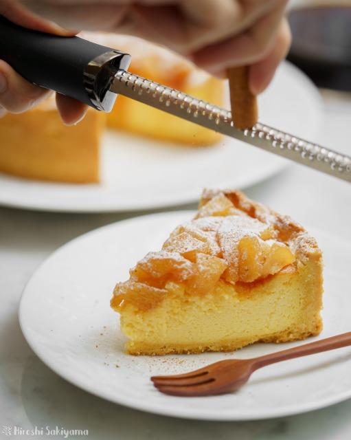 カラメル梨のチーズケーキタルトにシナモンをかける様子