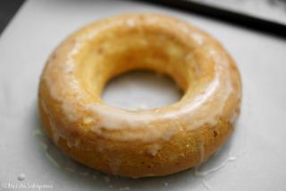 焼き上がったエンゼルフードケーキにオレンジのシロップで溶いた粉砂糖をかけた様子