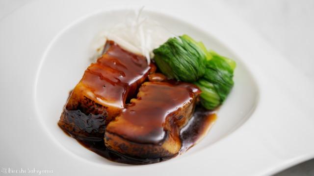 タレをかけるトンポーロー(東坡肉・豚の角煮)のアップ