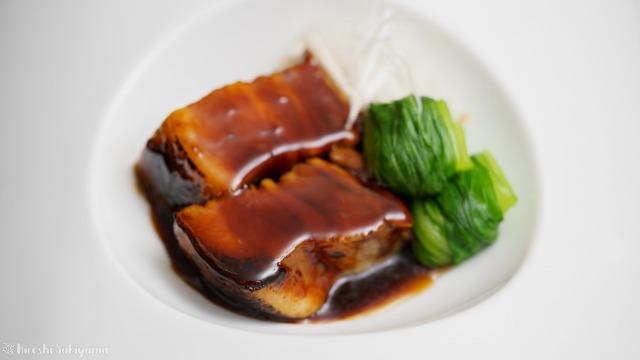 タレをかけるトンポーロー(東坡肉・豚の角煮)のどアップ