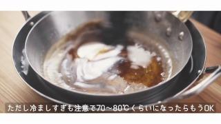 鍋の底を水に当て冷やす様子