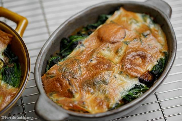 じゃがいも・茄子・ほうれん草のマッシュルームクリームチーズ焼きのアップ、灰色の皿