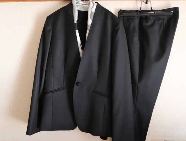 女性ミニマリストの通勤服(黒のパンツスーツとモノトーンスカーフ)