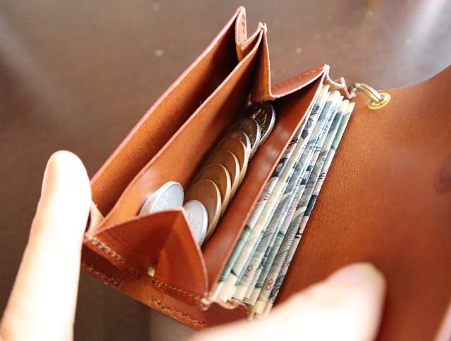 折りたたんだお札10枚、多めの小銭11枚が入った財布