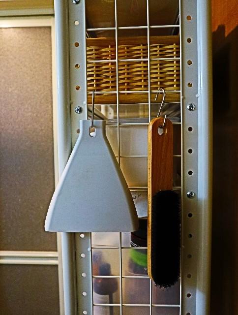 棚の側面に引っ掛けた掃除道具(ほうき・ちりとり・洋服ブラシ)
