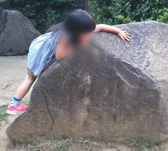 岩によじ登る娘