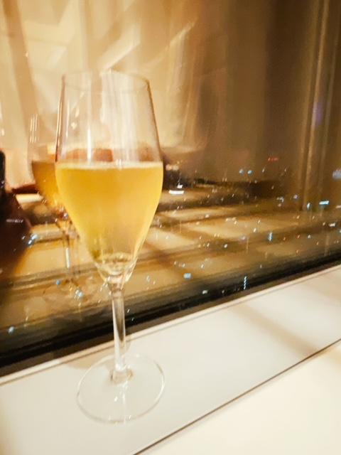 夜景と撮ったつもりがブレブレで酔いのほどが分かるグラスシャンパン