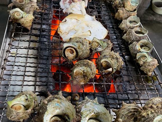 波戸岬売店内の網の上で焼かれているサザエやイカ