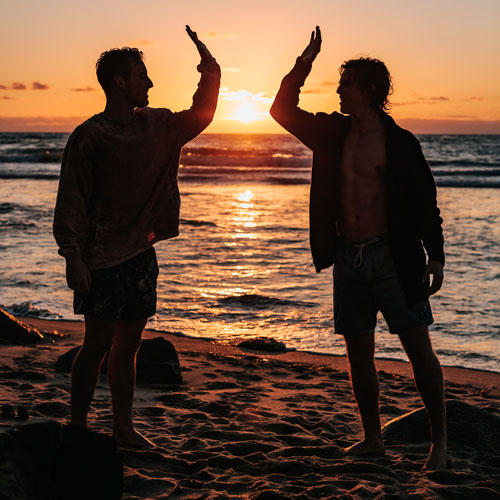 男同士が夕日の浜辺でハイ・ファイブする
