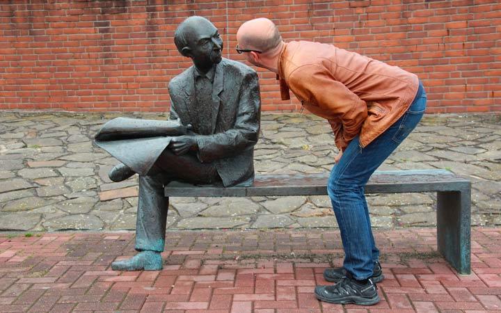 銅像に話しかける眼鏡の男性