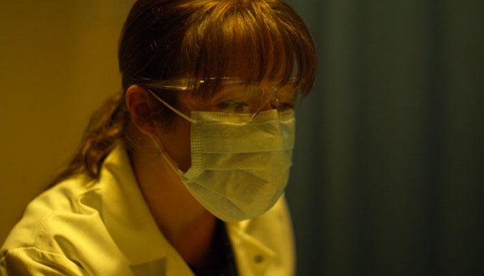 映画『コンテイジョン』で、女性医師がマスクをして患者を診察する