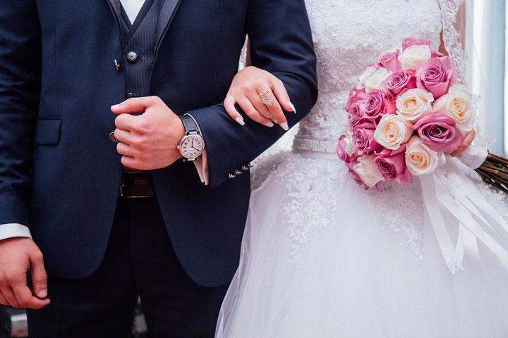 結婚式で腕を組み歩く新婚カップル