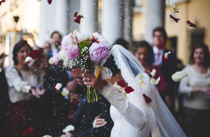 『参列者に祝福される中、教会を出ていく新婚カップル』