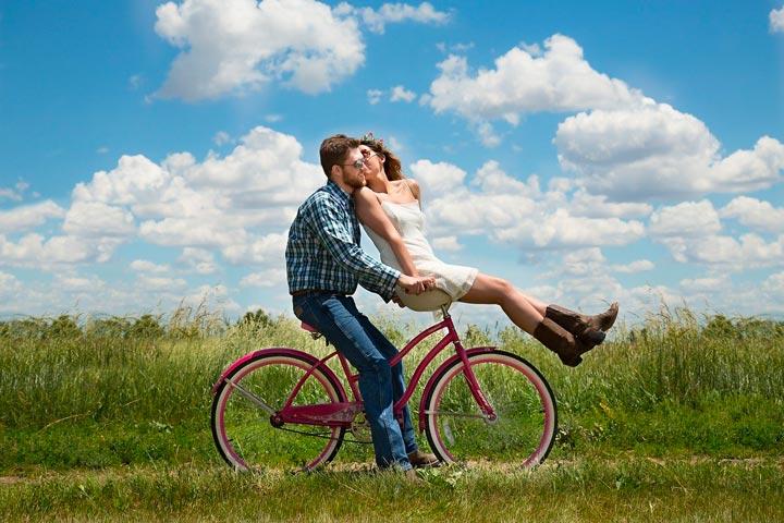 太陽の下、サイクリングに出かけてキスするカップル