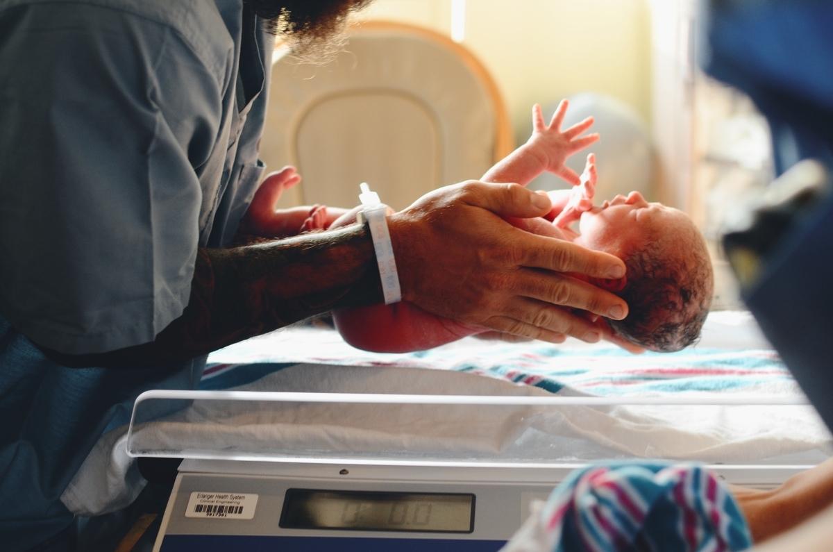 赤ちゃんを秤に乗せる画像