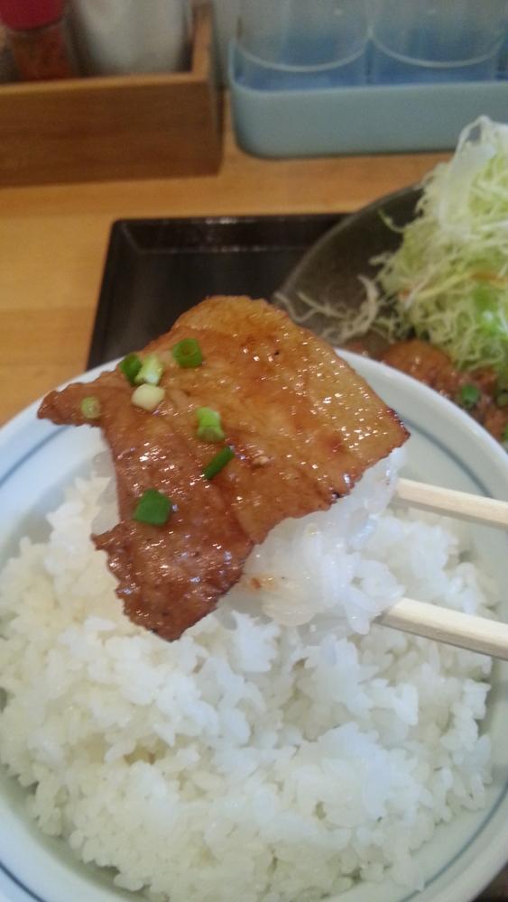 豚丼白樺の豚バラ肉をご飯にのせて箸で持ち上げた写真