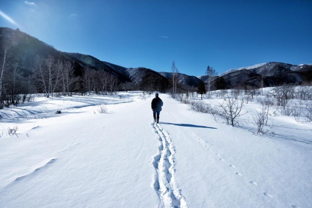 雪山を歩くスノーボード男性