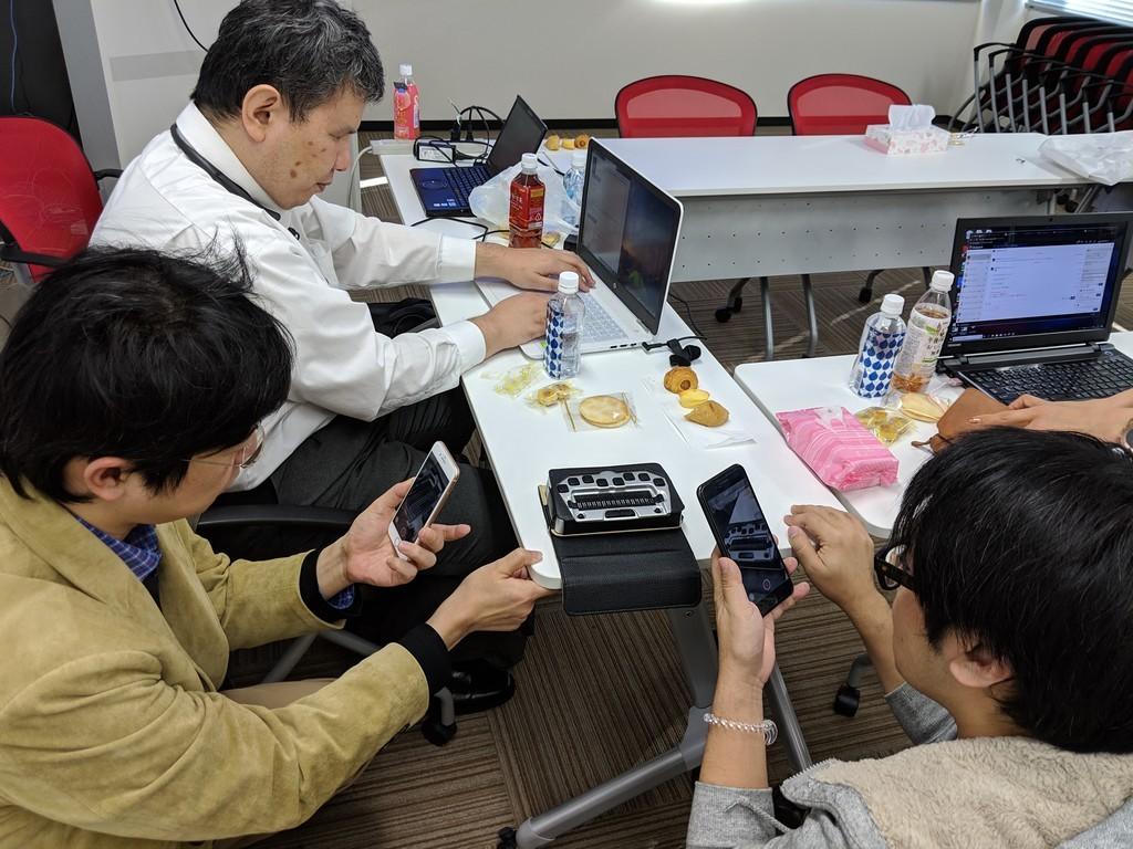 写真:辻さんがパソコンで点字ディスプレイを操作しているのを、太田さんと佐藤くんが動画を録っている
