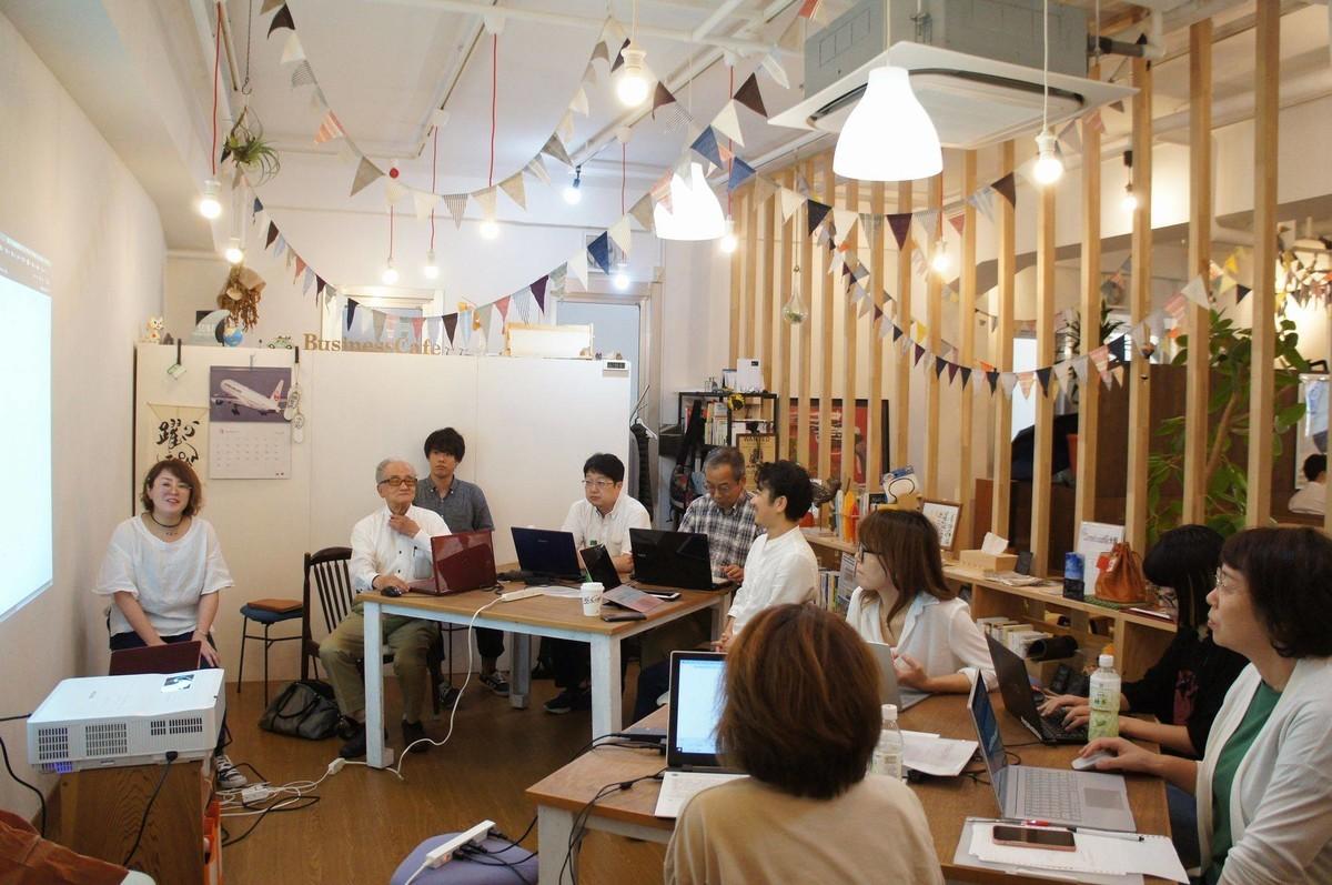 会場風景:白い壁にスライドを映して、その前でしゃべているいずいず。正方形のテーブルに各4名がパソコンを開いてスライドをみている