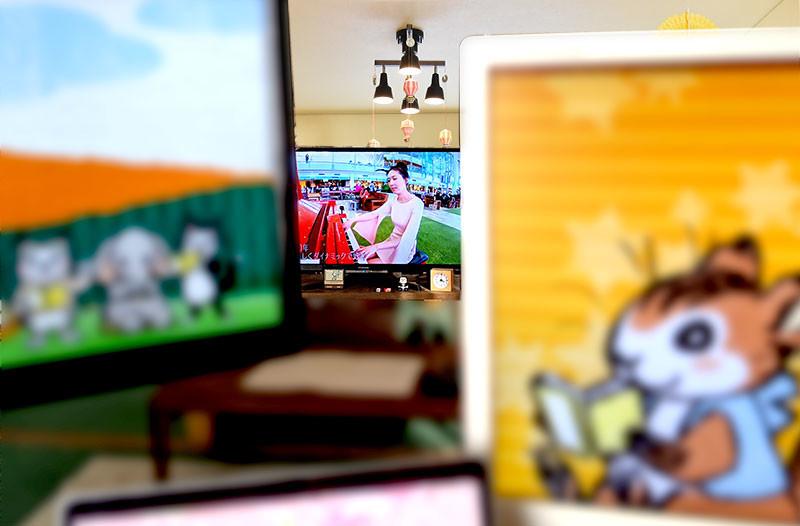 左手のディスプレイを少し左上に上げると、その先にテレビが見えてる。お部屋はぼかし処理しまくり。