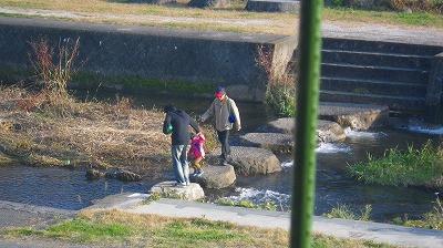 川を渡る親子とおじいちゃんの3人がいて