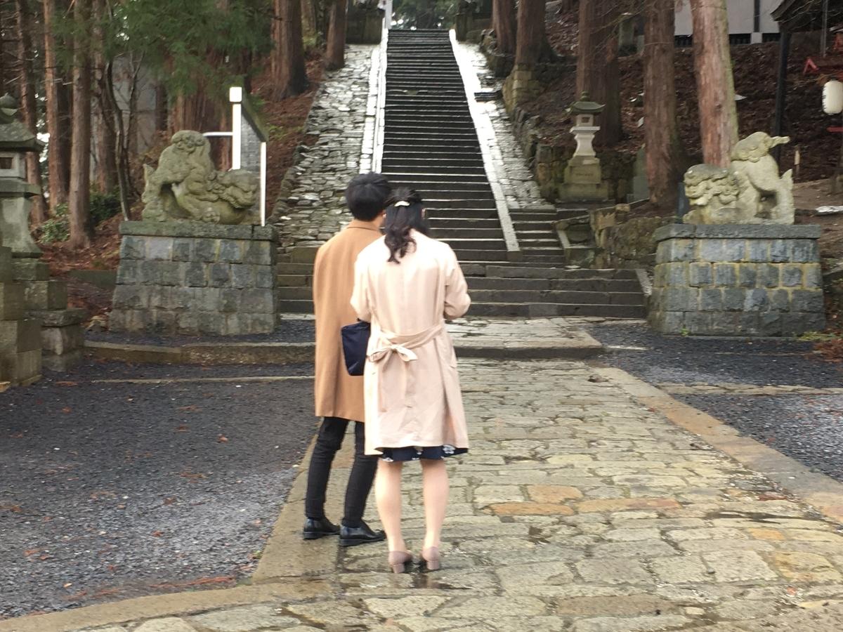 境内の階段の前に佇むカップル。