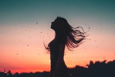 夕暮れに風にふかれる女性