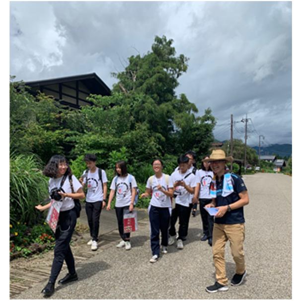 みなかみ町を訪れた海外からの学生と一緒に歩いて町内を案内する本連載筆者の阿部さん(右端)。あえて徒歩で移動するのは観光業以外の地域の人たちにも「実際に旅行や交流で海外から観光客が来ている」ことを知ってもらうため。この時に訪れたのは町と友好協定を締結している中国の大学の弓道交流団