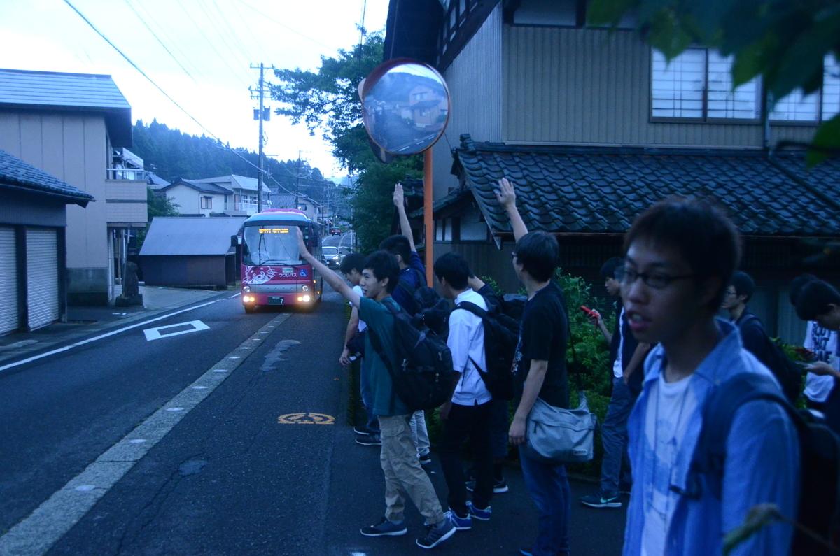 バスに向かって手を挙げる人々