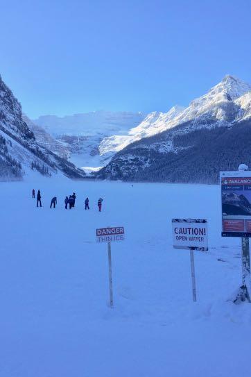 一面凍りついたレイク・ルイーズの上に人々が歩いている。遠くには氷河が見える。