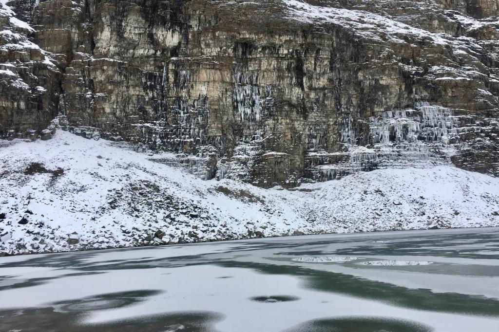 凍りついた湖とその後ろに氷柱の下がった岩肌。