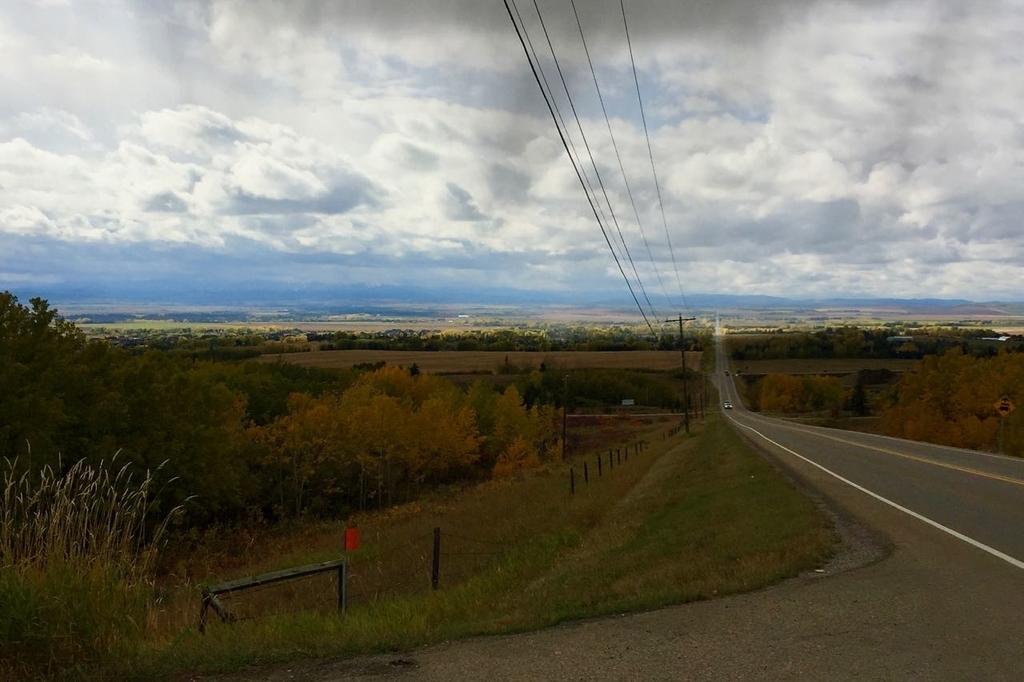 右端から中央へ向けて一直線に伸びる道路。その先にはロッキー山脈の山並み。そらは雲が多い。左側にはカルガリー郊外の牧場と所々黄葉した木々が見える。