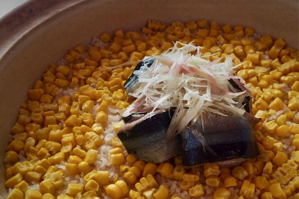 黄色いトウモロコシが敷き詰められて、中央には焼いたサンマと、その上に刻みミョウガが載せられてた土鍋の炊き込みご飯。