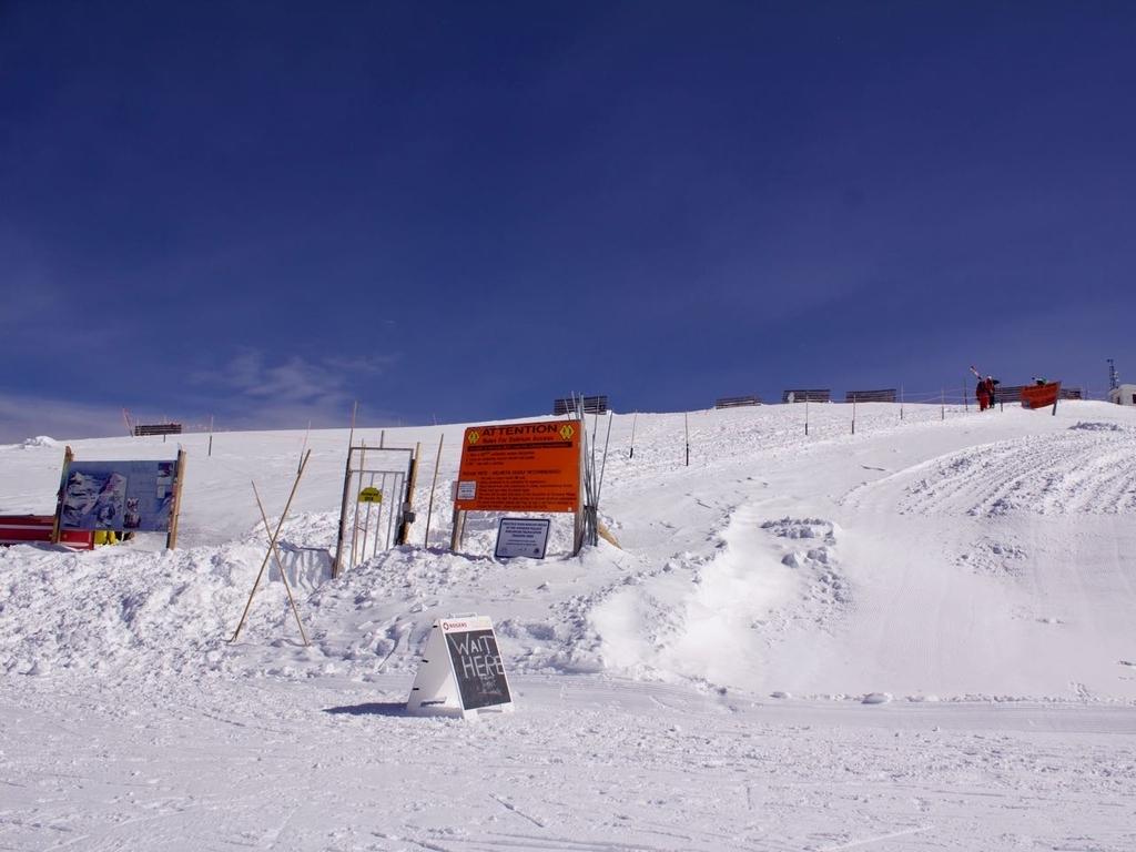 真っ青な青空と雪の斜面にオレンジの看板と鉄の扉が設置されている