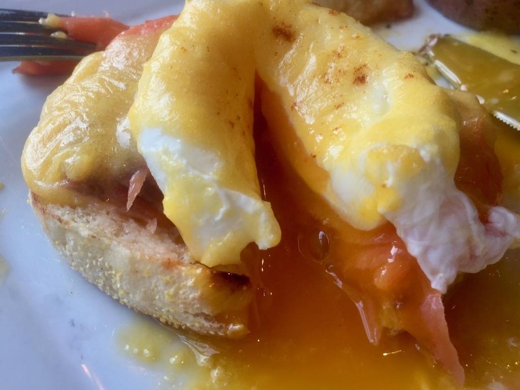 半分に切られたエッグベネディクトから卵黄が流れ出る
