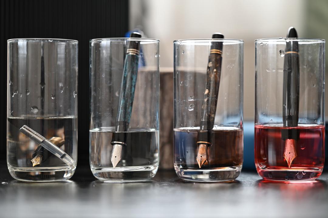 四つ並べてコップにそれぞれ水を張って、一本ずつ万年筆のペン先を浸けて洗浄してる。ペン先に溜まってた黒や茶、赤のインクが滲み出てる。