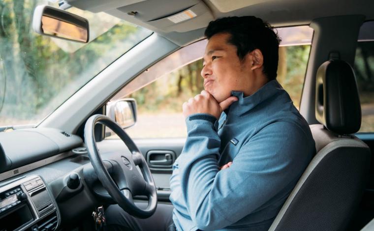 運転席で悩む男性