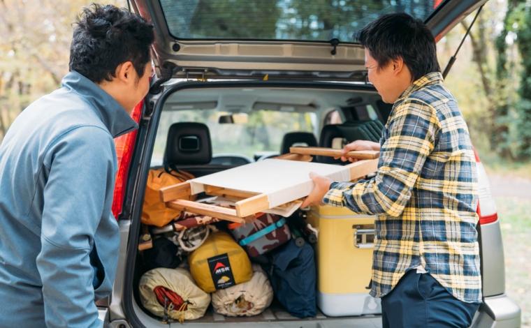 車にキャンプ道具を積載する男性