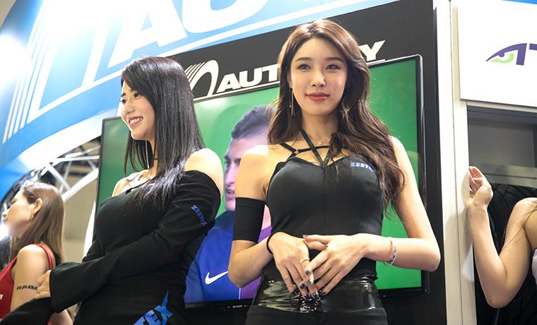 東京オートサロンの黒い服の美女の画像です。