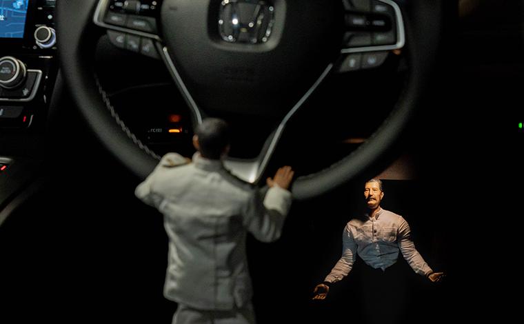 ホンダ新型インサイトの運転席下にたたずむヨシダさんを見つめるミフネさん